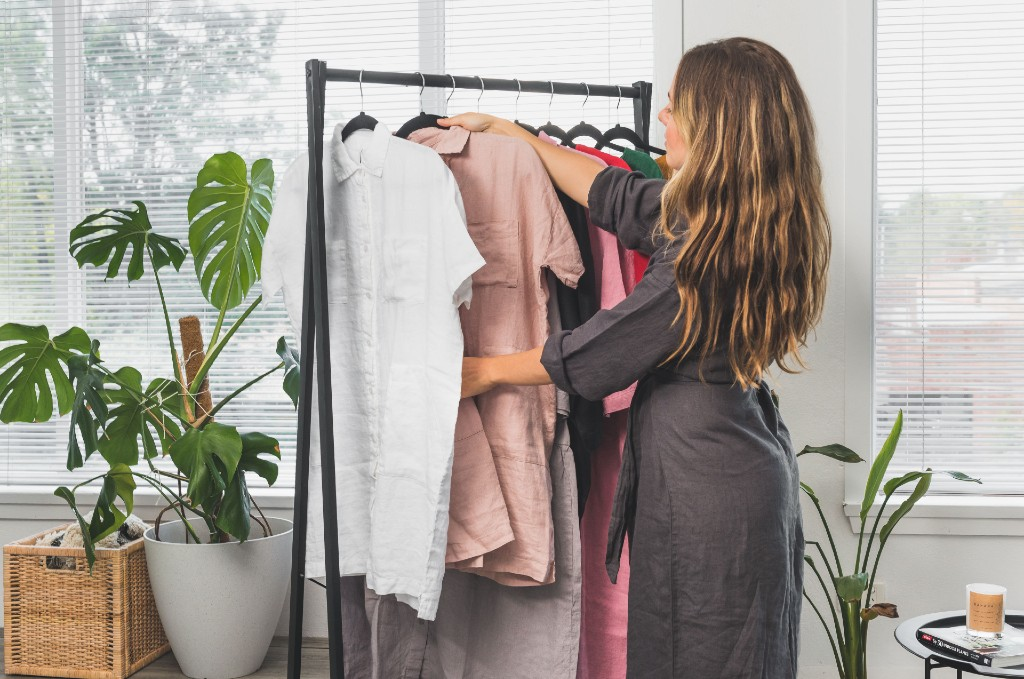 Lady hangs up linen shirt on rack with other clothes