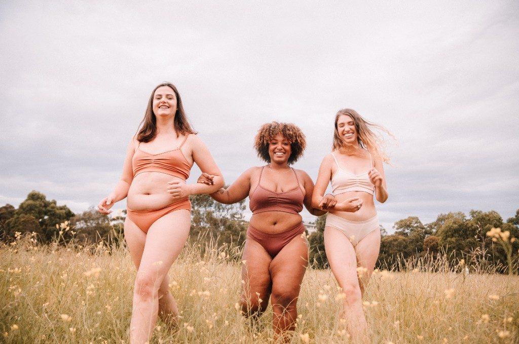 Three models in a field wearing neutral coloured underwear