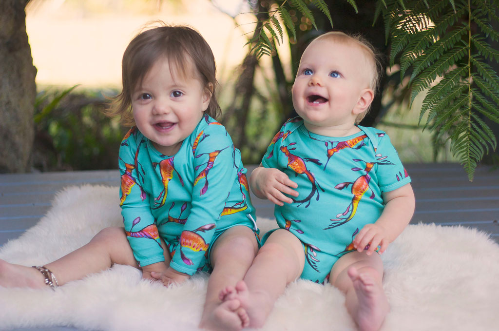 Two babies laughing in the sand