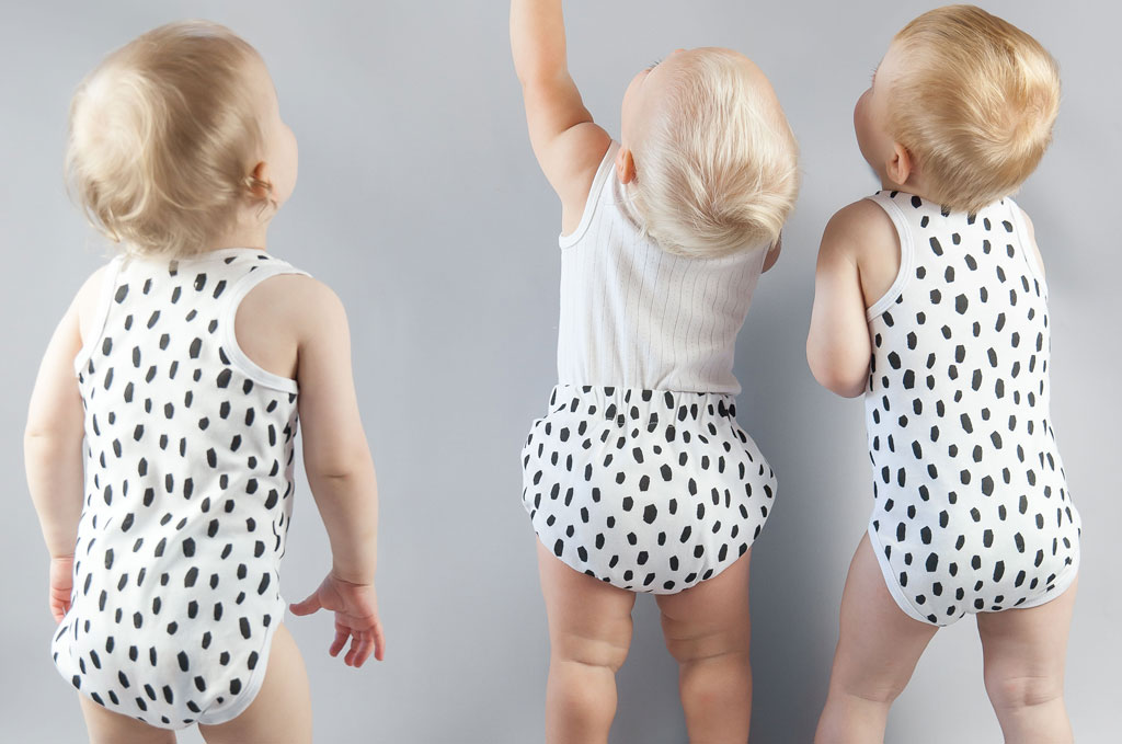 Three babies facing the wall with spotted outfits